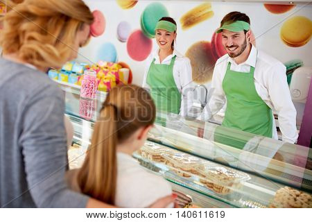Female and male sellers and customers in confectionery