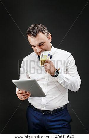 Portrait of nervous businessman looking at tablet while biting banknote. Studio shot