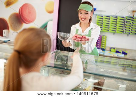 Saleswoman serves young customer with macarons in pastry shop