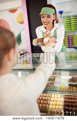 Smiling saleswoman gives macarons to young customer in bakery