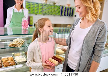 Young mother with daughter in beautiful pastry shop