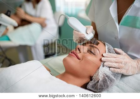 Cavitation peeling, beauty treatment on face,  woman's face during a facial at a beauty salon