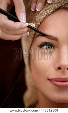 Pretty woman receiving professional drawing eyebrows, make up
