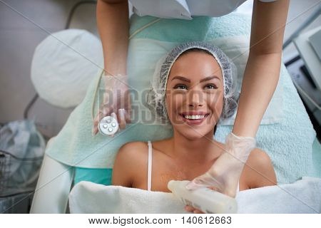 Cheerful girl is receiving  facial treatment by beautician, lady lying and smiling 4D laser lifting face