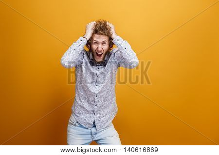 Portrait of male model tearing hair in hysteria on yellow background. Isolated. Big sale concept.