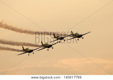 BUCHAREST (ROMANIA) - 30 JUNE 2016: Silhouette of airplanes (Aeroclub Roman Team) performing acrobatic flight at sundown. Trace of Smoke behind it