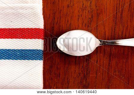 Teaspoon Salt And White Napkin On Wood