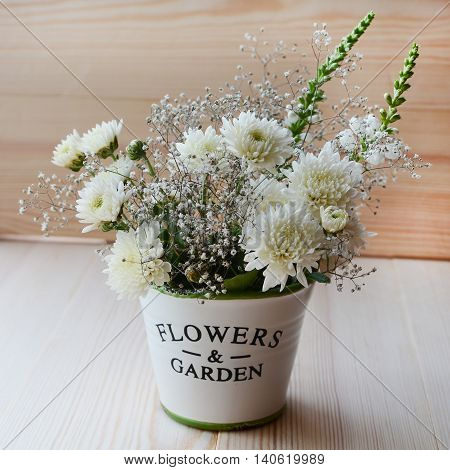 White chrysanthemum flowers in a decorative pot on a wood background
