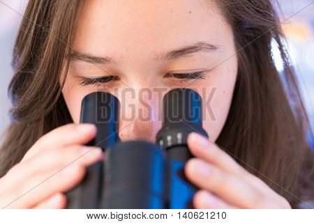 Biology lesson. Female Teenage Student In Science Class With Experiment on Microscope