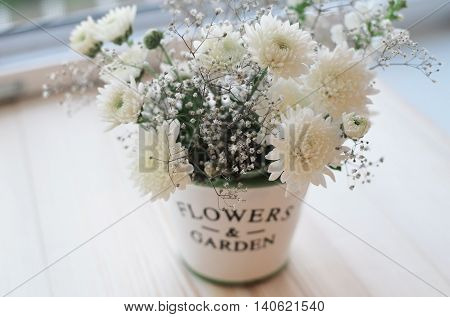 White chrysanthemum flowers in a decorative pot on a wood window sill