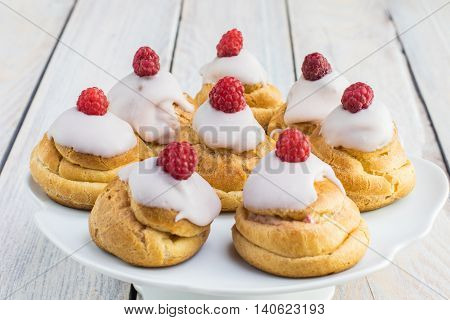 Raspberries Profiterole with White Chocolate on Plate on White Table