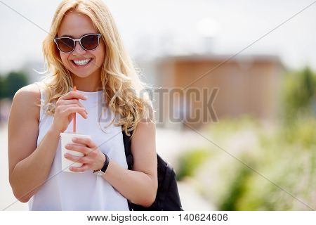 Portrait of laughing young blond woman in white blouse with refreshing drink outdoors