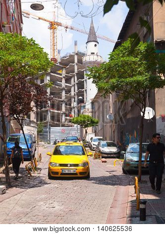 Yellow Taxi Car Goes On Narrow Street In Old Istanbul