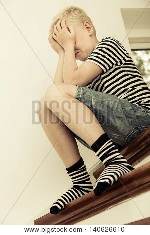 Seated Boy Wearing Stripped Shirt And Socks
