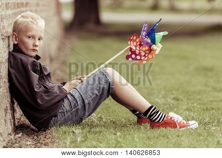 Sad Blond Boy Sits Against Wall Holding Whirligig