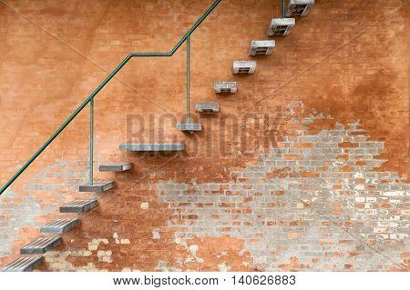A metal stairway on an orange brickwall