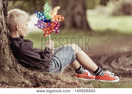 Blond Boy Holding Colorful Whirligig Sits By Tree