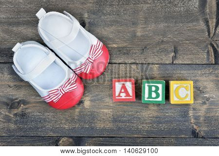 Kid shoes and word ABC on wooden table