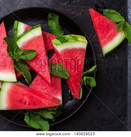 Still life, food and drink, diet concept. Organic fresh watermelon slices with mint on a grunge black table. Selective focus, top view