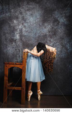 Ballerina Tying Ballet Shoes.Ballet dancer in blue skirt