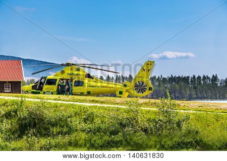 Klövsjö, Jämtland, Sweden - July 25, 2016: Paramedics helping patient into helicopter. Ambulance helicopter next to cabin, paramedics and patient.