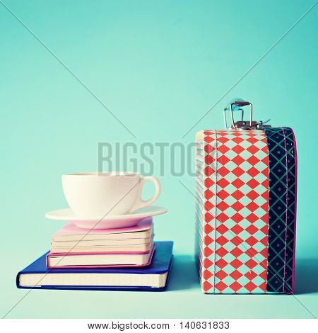 Vintage lunchbox and tea cup over notebooks