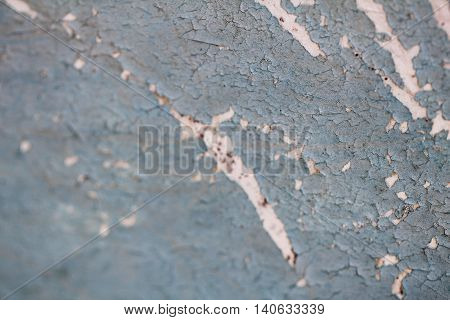 Cracked paint on blue wooden surface close up photo