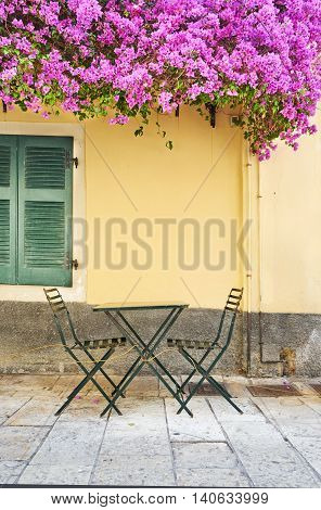 Old traditional greek house and chairs with flowers of bougainvillea Corfu Greece