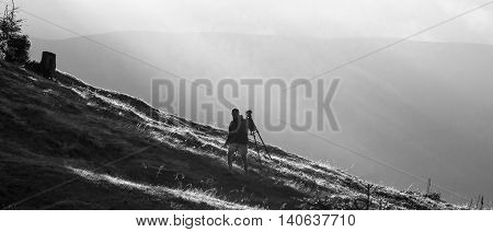 Photographer with camera on tripod in mountains under sun rays black and white photo
