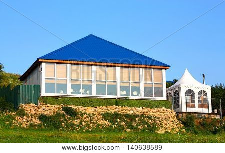 Tent with a blue roof and white tent nearby on a background of trees