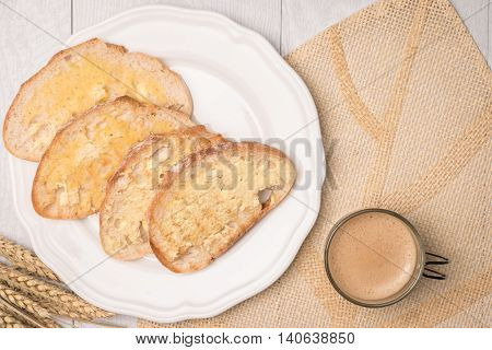 Fresh bread homemade butter and coffee on wooden background. Top view with copy space.