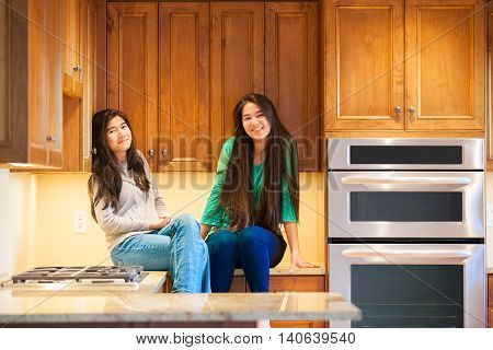 Two smiling biracial Asian Caucasian teen girls sitting on counter in modern kitchen next to wall ovens