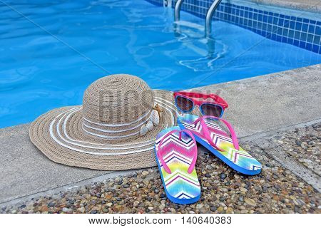 Woman's hat with sunglasses and flip-flops by swimming pool.