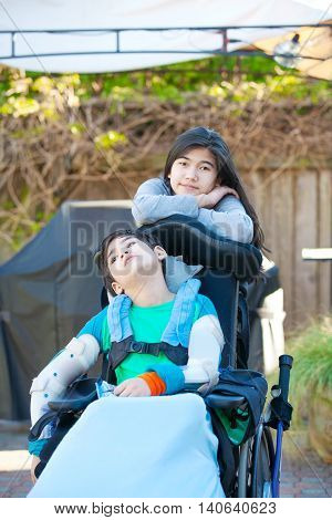 Teenage sister taking care of disabled brother in wheelchair outdoors in yard