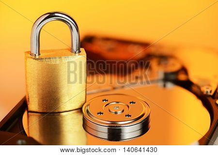Gold padlock on the opened HDD disk drive surface. Data protection or security concept