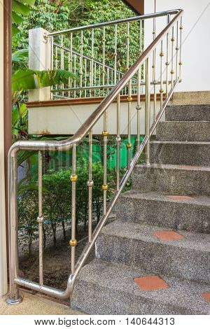Steel railing on a smail stone staircase leading to the balcony