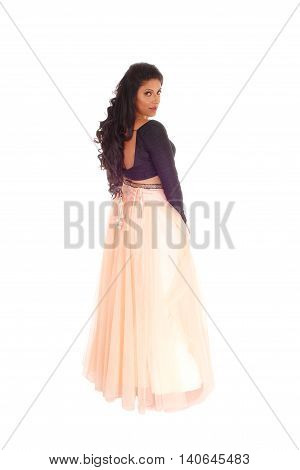 A pretty woman in a black blouse and long pink skirt standing from back looking over her shoulder isolated for white background.