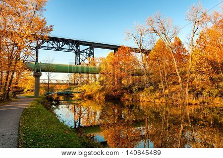The Ohio Canal flows placidly under a railroad trestle and sewage pipe near Cleveland on a late autumn afternoon