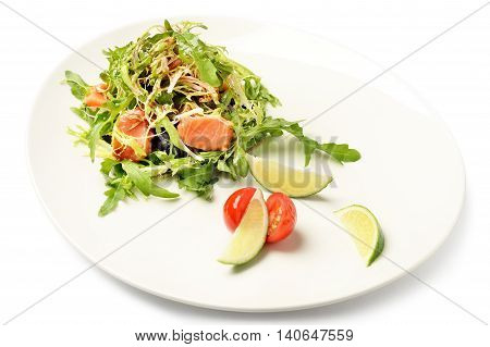 Salmon and ruccola fresh salad served with lime and cherry tomato slices on plate isolated on white