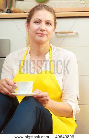 Mature woman in apron with cup of coffee in kitchen. Housewife female relaxing resting sitting on floor.