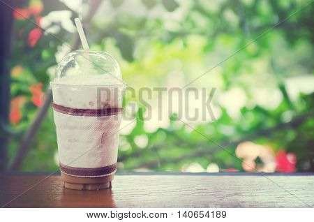 Cold coffee cup on the wooden table with bokeh background in coffee shop filter apply
