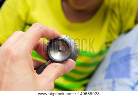Doctor stethoscope in preparation to hear at a girl chest