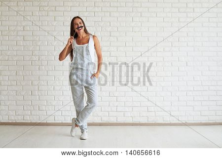 Smiling beautiful woman wear strip overalls standing with one foot on tiptoe and holding mustache near her face, white brick wall on background