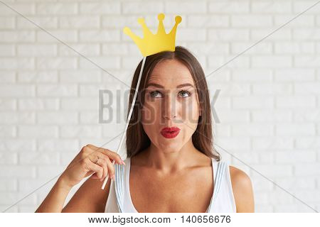 Amazing woman dreaming and holding decorate crown, white brick wall on background