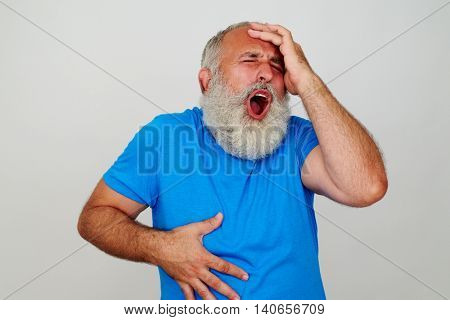 Expressive elderly bearded man is gesturing head and stomach ache against white background
