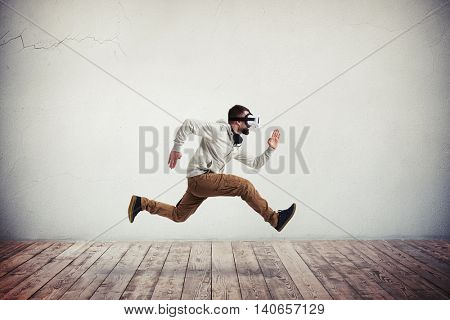 Young bearded man in virtual reality headset is photographed in mid-air jump over wooden floor and white wall background