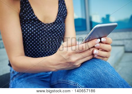 A modern young girl checking email via smart phone. Nowadays most people run their lives using their smartphone, from planning routines or keeping up-to-date with what is going on.