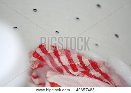 Red and white cloth clinging to the side of a washing machine as it spins with soap suds around it's edges