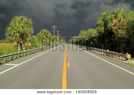Tamiami Trail heading into an ominous thunderstorm in the Florida Everglades, Collier County