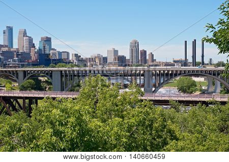 skyline of downtown minneapolis with tenth avenue and pedestrian bridge spanning mississippi river from east river road